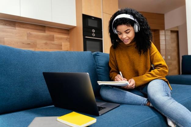 Adolescente avec ordinateur portable et écouteurs pendant l'école en ligne