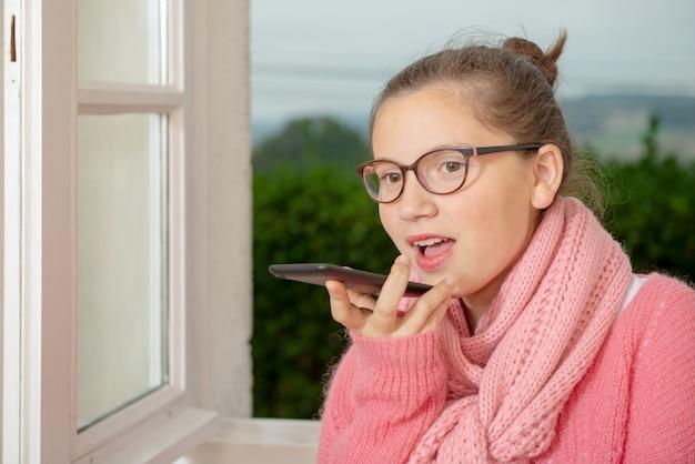 Adolescente parlant avec un smartphone près de la fenêtre