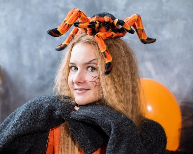 Adolescente parmi le décor pour les vacances d'halloween, énorme araignée sur la tête. gros plan photo, couleurs noir orange