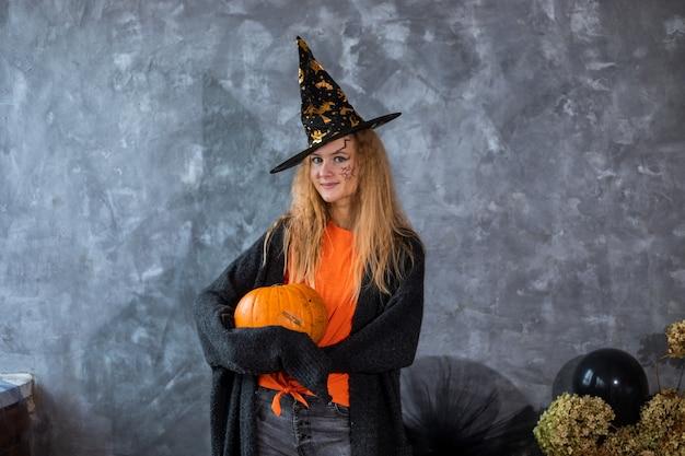 Adolescente parmi le décor pour les vacances d'halloween, énorme citrouille à la main. gros plan photo