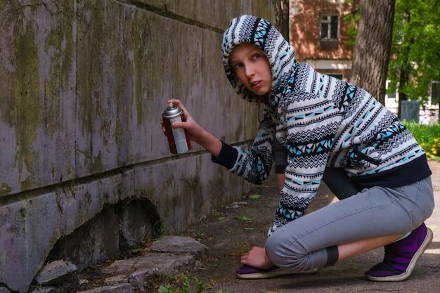 Une adolescente avec de la peinture en aérosol regarde autour d'elle, sur le point d'écrire des graffitis sur le mur