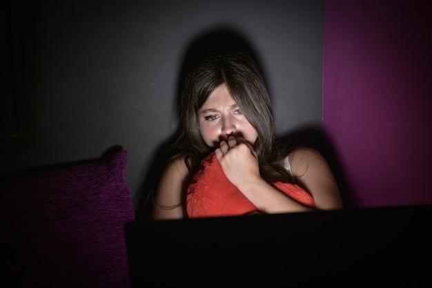 Une adolescente a peur de regarder un film d'horreur