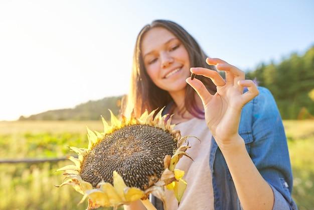 Une adolescente avec une plante de tournesol mûre, une femelle montre une graine noire mûre. fond de paysage naturel d'automne, coucher de soleil, heure d'or