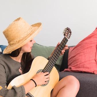 Adolescente, porter, chapeau, séance, sofa, jouer guitare