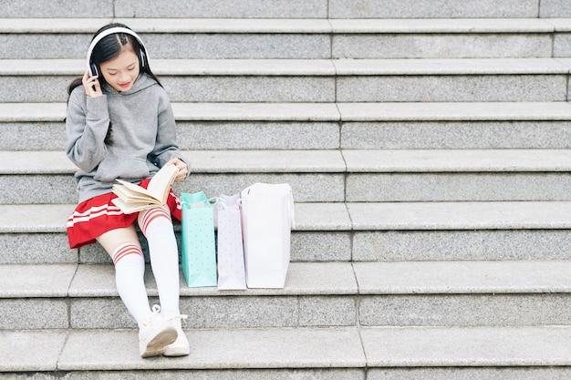 Adolescente positive dans les écouteurs assis sur les marches et lisant un livre intéressant après les cours