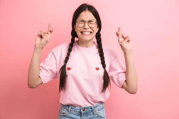 Adolescente positive avec deux tresses portant des lunettes souriant et gardant les doigts croisés pour jurer isolé sur un mur rose