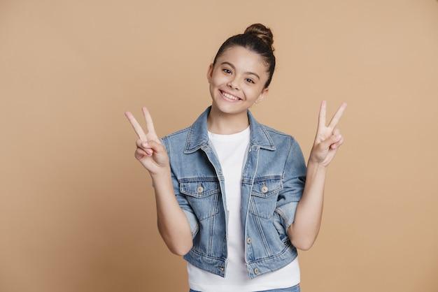 Adolescente positive et souriante montrant le geste en v. la fille gesticule joyeusement sur un fond marron