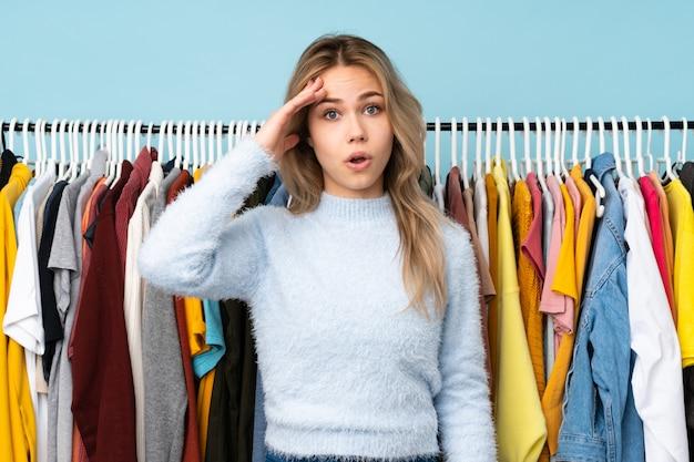 Une adolescente qui achète des vêtements sur le mur bleu vient de réaliser quelque chose et a l'intention de trouver la solution