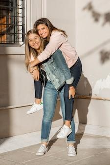Adolescente qui donne à sa petite amie une promenade en ferroutage debout devant le mur