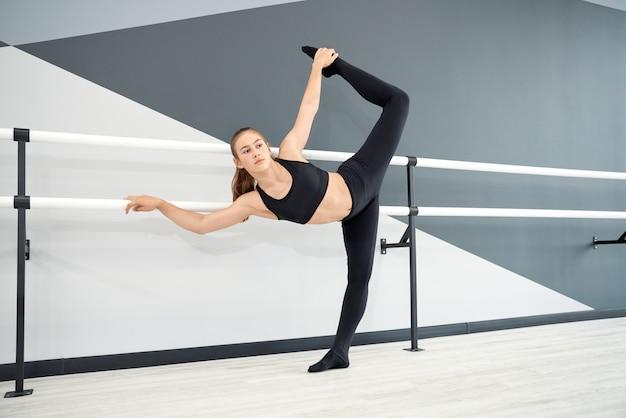 Adolescente qui s'étend dans la salle de ballet
