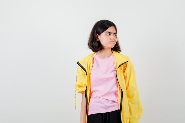 Adolescente regardant de côté en t-shirt, veste et hésitante, vue de face.