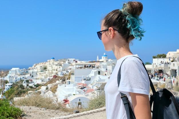 Adolescente reposant sur l'île grecque de santorin, femme regardant loin, arrière-plan architecture blanche du village d'oia, mer, ciel dans les nuages, espace pour copie