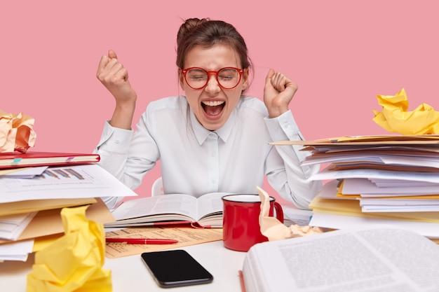 Adolescente réussie serre les poings avec triomphe, beig en haute spirt, célèbre le travail de projet bien fait, s'assoit au bureau avec un livre ouvert et des documents papier