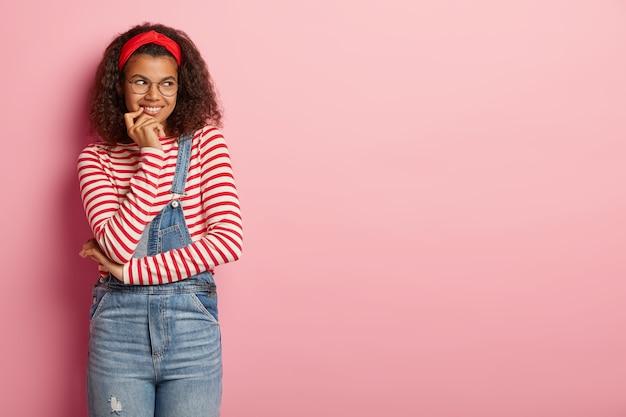 Adolescente rêveuse posant en salopette aux cheveux bouclés