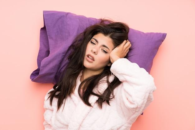 Adolescente en robe de chambre sur fond rose et stressée
