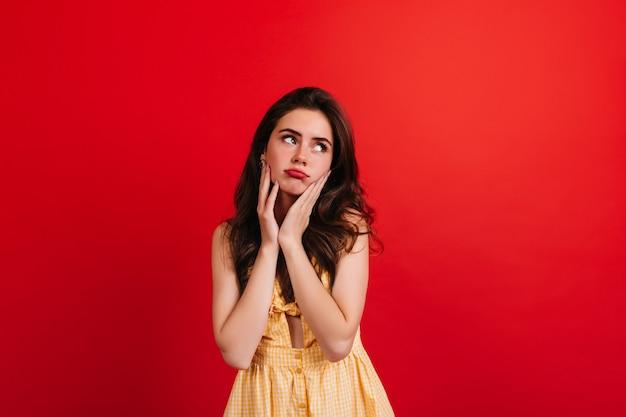 Adolescente en robe d'été jaune posant de mauvaise humeur contre le mur rouge. closeup portrait de femme brune aux lèvres rouges.