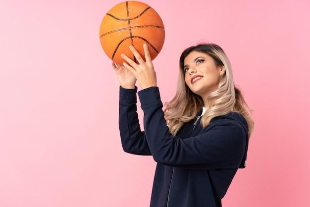 Adolescente sur rose isolé avec ballon de basket