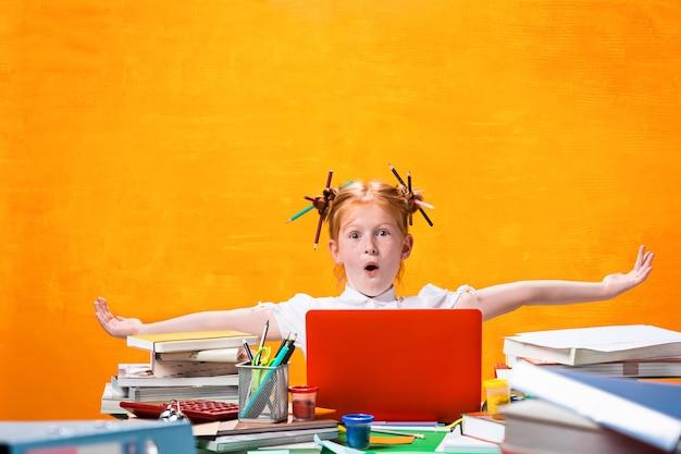 L'adolescente rousse avec beaucoup de livres à la maison. prise de vue en studio