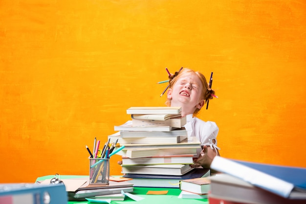 Adolescente rousse avec beaucoup de livres à la maison