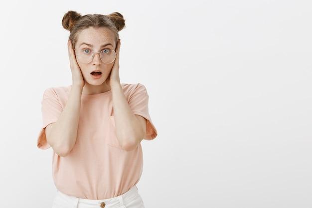 Adolescente rousse choquée et embusquée posant contre le mur blanc