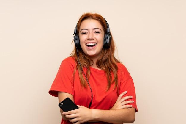 Adolescente rousse écoute de la musique avec un téléphone portable sur un mur isolé