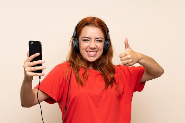 Adolescente rousse écoute de la musique avec un téléphone portable avec le pouce vers le haut