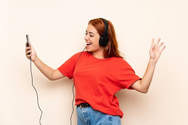 Adolescente rousse écouter de la musique avec un mobile sur isolé