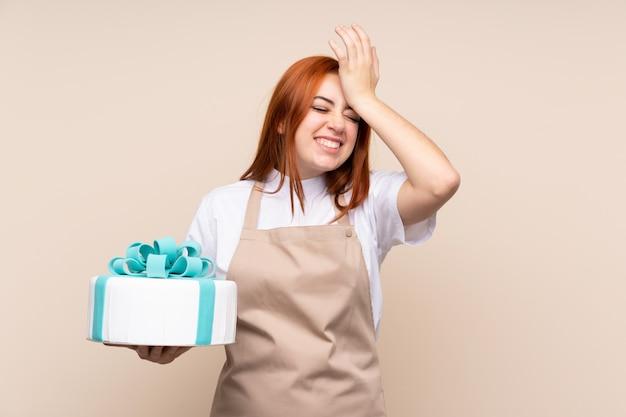 Adolescente rousse avec un gros gâteau sur un mur isolé a réalisé quelque chose et a l'intention de la solution