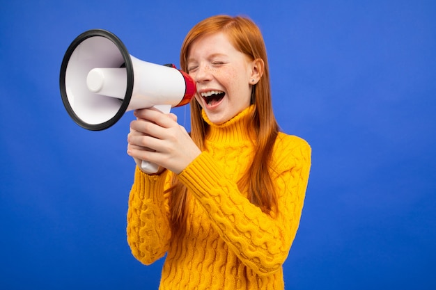 Adolescente rousse hurlant les yeux fermés au haut-parleur de nouvelles sur un fond de studio bleu