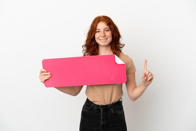 Adolescente rousse isolée sur fond blanc tenant une pancarte vide