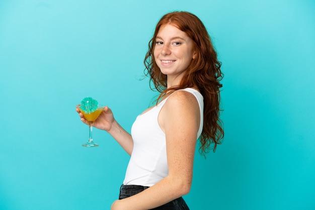 Adolescente rousse isolée sur fond bleu en maillot de bain et tenant un cocktail