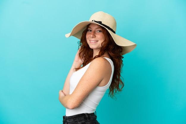 Adolescente rousse isolée sur fond bleu en maillot de bain en vacances d'été