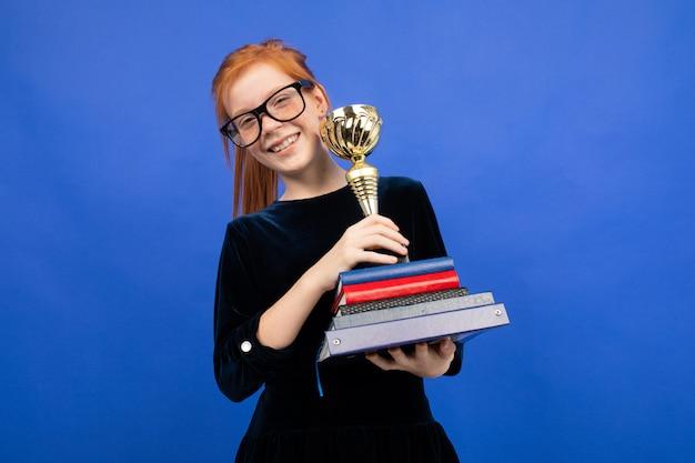 Adolescente rousse joyeuse avec une pile de livres et une tasse de victoire sur bleu