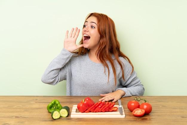 Adolescente rousse avec des légumes sur une table en criant avec la bouche grande ouverte