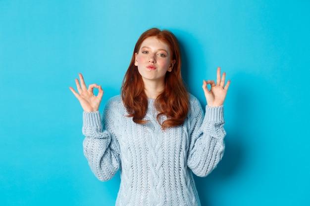 Adolescente rousse montrant des signes corrects, l'air satisfaite et fière, d'accord, donne une réponse positive, louant le bon choix, debout sur fond bleu