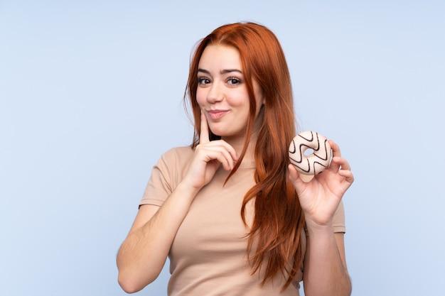 Adolescente rousse sur mur bleu isolé tenant un beignet