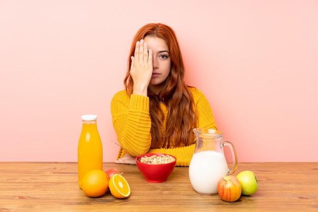 Adolescente rousse prenant son petit déjeuner dans une table couvrant un oeil à la main