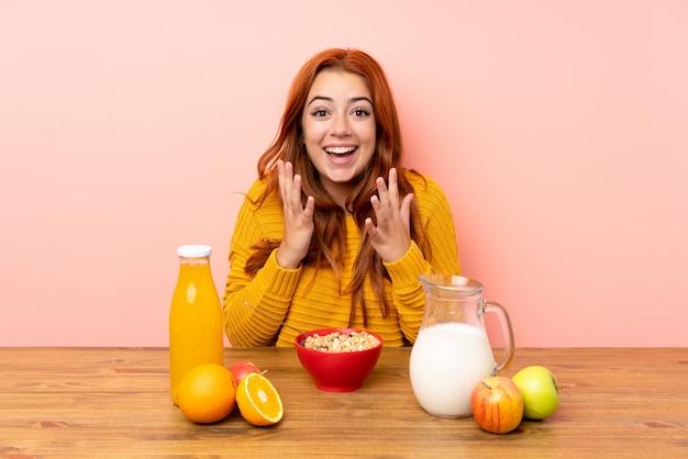 Adolescente rousse prenant son petit déjeuner dans une table avec une expression faciale surprise