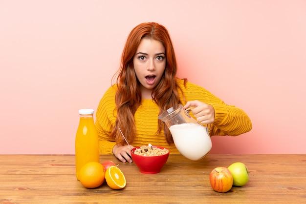 Adolescente rousse prenant son petit déjeuner dans une table