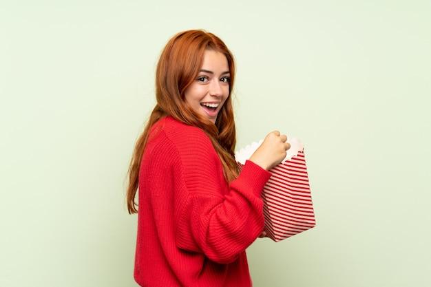 Adolescente rousse avec pull sur mur vert isolé, manger des pop-corn