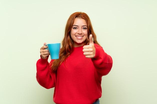 Adolescente rousse avec pull sur vert isolé tenant une tasse de café chaude