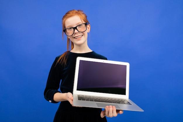 Adolescente rousse souriante dans des verres est titulaire d'un ordinateur portable avec un écran blanc