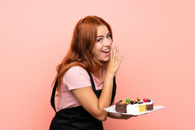 Adolescente rousse tenant beaucoup de différents mini gâteaux sur rose isolé chuchotant quelque chose