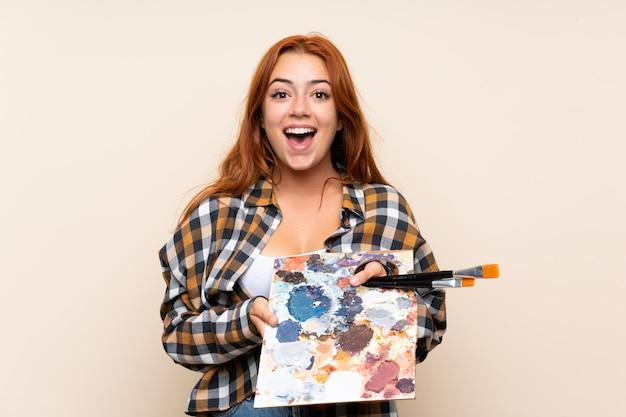 Adolescente rousse tenant une palette avec une expression faciale surprise