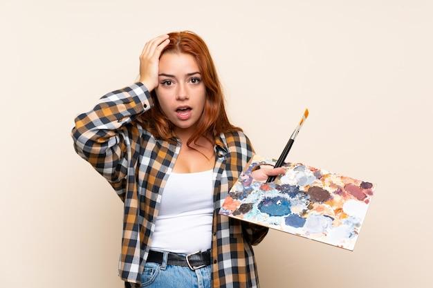 Adolescente rousse tenant une palette sur un mur isolé avec une expression faciale surprise