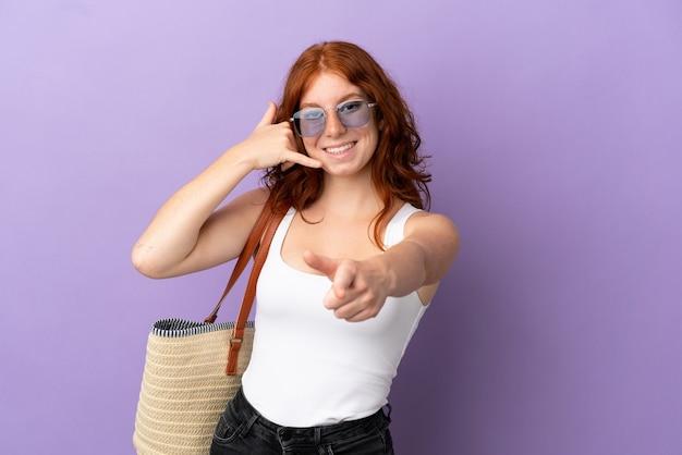 Adolescente rousse tenant un sac de plage isolé sur fond violet faisant un geste de téléphone et pointant vers l'avant