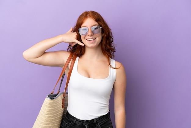 Adolescente rousse tenant un sac de plage isolé sur fond violet faisant un geste de téléphone. rappelle-moi signe