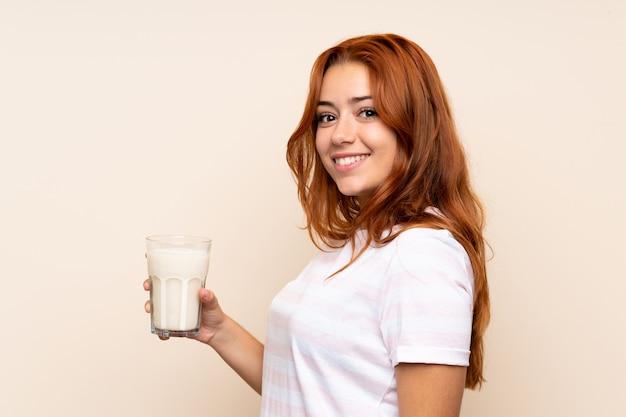 Adolescente rousse tenant un verre de lait souriant beaucoup