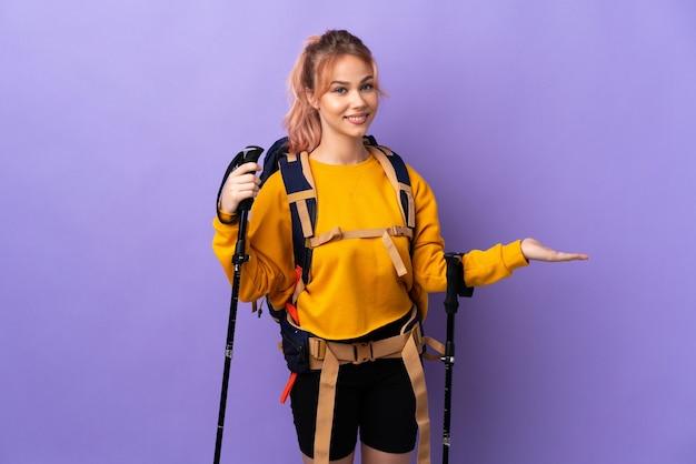 Adolescente avec sac à dos et bâtons de randonnée sur mur violet isolé étendant les mains sur le côté pour inviter à venir