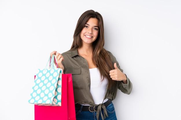 Adolescente avec sac à provisions avec les pouces vers le haut parce que quelque chose de bien s'est produit